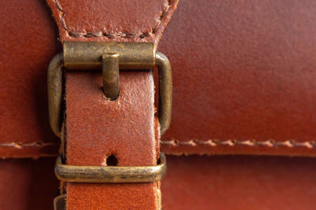 Fashionable brown womens bag made of genuine leather close-up. Fashion concept. Details of leather bag, belt, metal buckle, clasp, thread stitching, macro shot. Stylish female accessory