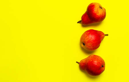Juicy ripe fresh red pears on yellow background flat lay top view copy space. Creative background with pears and green leaves. Fruit background, organic healthy food. Harvest concept