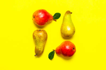 Juicy ripe fresh green and red pears on yellow background flat lay top view copy space. Creative background with pears and green leaves. Fruit background, organic healthy food. Harvest concept