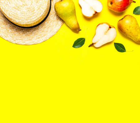 Ripe fresh green red pears, straw hat on yellow background flat lay top view copy space. Fruit background, organic healthy food. Harvest concept. Creative background with pears and green leaves