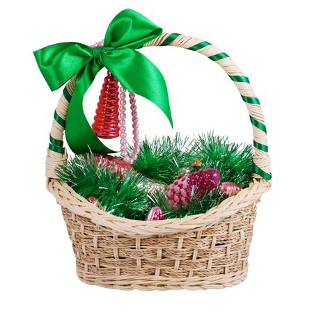 Christmas basket with bow, assorted ornaments. Isolated. Stock Photo