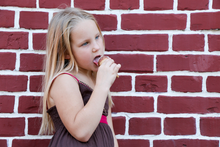 little beautiful girl eats an ice cream on a brick wall background in a brown dress, in summer