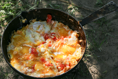 Breakfast on nature of picnic, hiking food. Scrambled egg fried on coals in pan on open fire, cook over an open fire Stok Fotoğraf