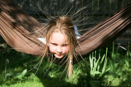 beautiful little girl with blond hair resting in a hammock in summer sunny day