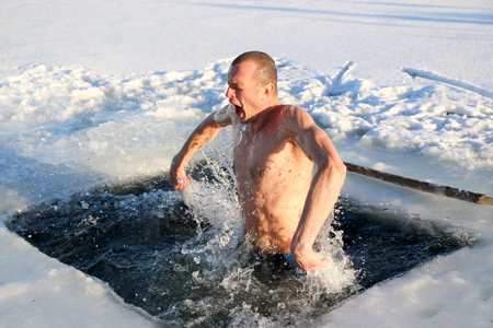 A young, slim, handsome, strong, athletic man, naked, diving into the icy water in the winter, against a snowy landscape, a bright sunny day, many beautiful drops and splashes. Ukraine, Shostka Фото со стока