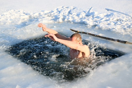 A young, slim, handsome, strong, athletic man, naked, diving into the icy water in the winter, against a snowy landscape, a bright sunny day, many beautiful drops and splashes. Ukraine, Shostka Stockfoto