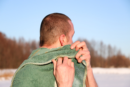 Young Good Looking And Attractive Man With Muscular Body, Taking after taking an ice bath. handsome attractive men showering next to swimming pool. water drops are falling on his torso. Sunny winter day in Ukraine, Shostka Stockfoto