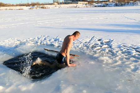 young, slim, handsome, sporty man , naked, in the winter after diving into the icy water, amid the snowy industrial landscape, Ukraine, Shostka