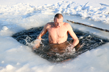 A young, slim, handsome, strong, athletic man, naked, diving into the icy water in the winter, against a snowy landscape, a bright sunny day, many beautiful drops and splashes. Ukraine, Shostka 版權商用圖片