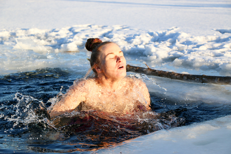 A beautiful young girl, with red hair, a side-piece swimsuit, dives into the icy water in the winter on the lake on a beautiful sunny day. Ukraine, Sumy Oblast, Shostka