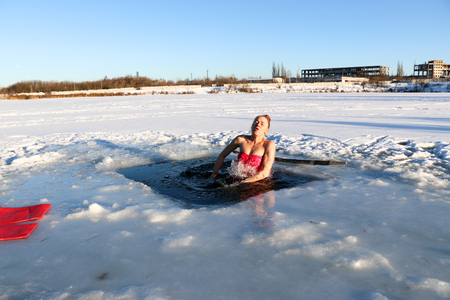 A beautiful young girl, with red hair, a side-piece swimsuit, dives into the icy water in the winter on the lake on a beautiful sunny day. Ukraine, Sumy Oblast, Shostka Foto de archivo
