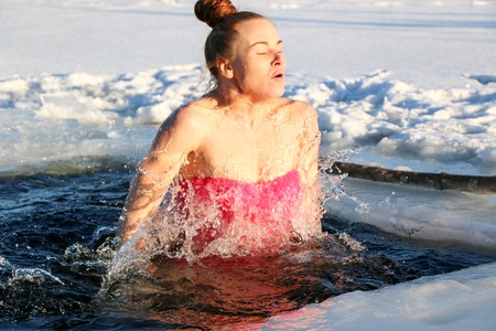 A beautiful young girl, with red hair, a side-piece swimsuit, dives into the icy water in the winter on the lake on a beautiful sunny day. Ukraine, Sumy Oblast, Shostka 免版税图像