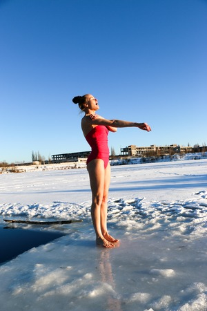 A beautiful young girl, with red hair, a pink swimsuit, getting ready to dive into the icy water in the winter on the lake on a beautiful sunny day. Ukraine, Sumy Oblast, Shostka