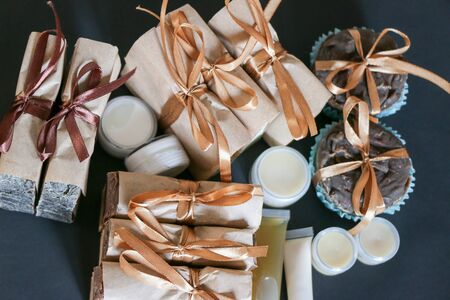 A set of natural cosmetics of body care in gift wrap: soap, cream, jar shampoo, conditioner, shower gel, scrub, lotion isolated. Beauty treatment. on a black background