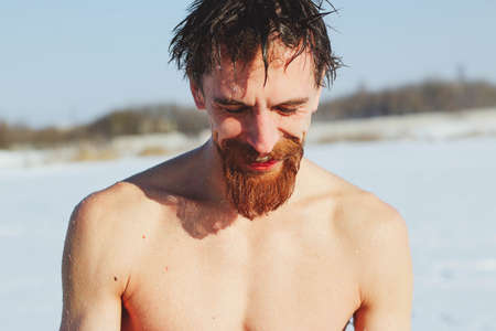 young, slim, handsome, sporty man with a red beard and long hair, naked, diving after a swim in icy water, on a sunny frosty day into ice-cold water in winter, against the backdrop Ukraine, Shostka