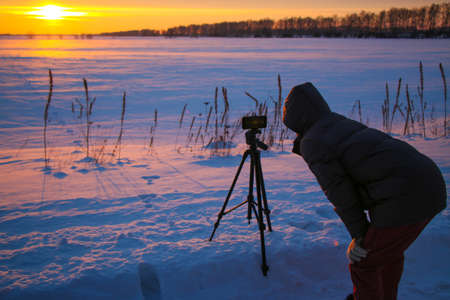 Man with phone on tripod making time-lapse photographs of winter zidio sunset. The field, road and trees are covered with snow.