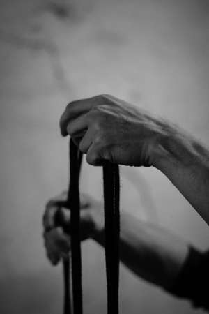 A man holds black shibari ropes in his hand, winds and ties. black and white photo