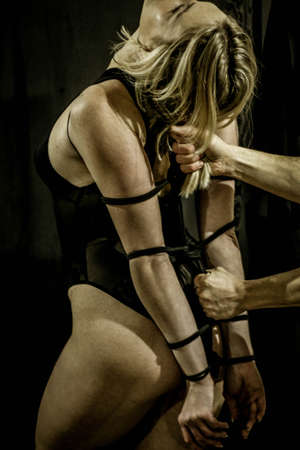 Bridge of Confidence, Shibari Dragonfly, A woman wrapped in a traditional Japanese shibari, tied with a rope, kinbaku. photo tying process, male hands
