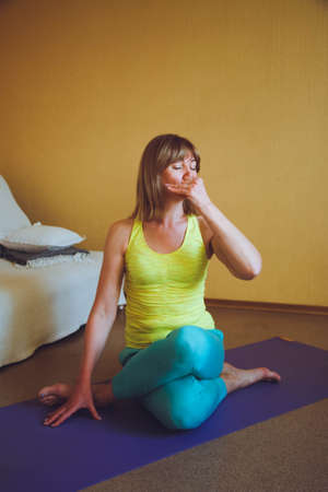 adult beautiful European Woman practicing home yoga. A series of yoga poses. cow head pose Gomukhasana healthy lifestyle concept, wellness self-care