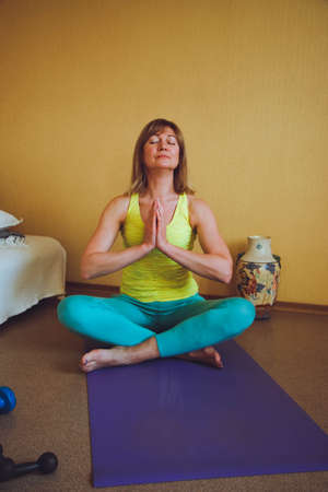 adult beautiful European Woman practicing home yoga. A series of yoga poses. meditates pranayama breathing exercise Ardha Padmasana healthy lifestyle concept, wellness self-care