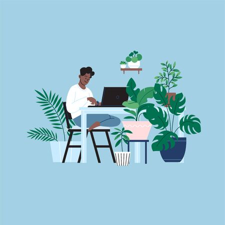 A person staying home working on the laptop in the kitchen. A room full of plants.