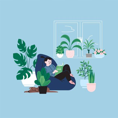 A girl staying home reading a book by the window sitting in the bean bag chair. A room full of plants.