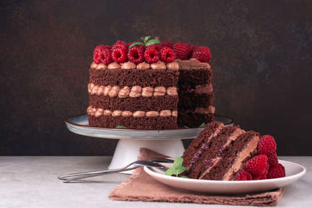 Chocolate cake with raspberries and butter cream on white table and dark backdrop. Piece of cake on a plate. Copy space.