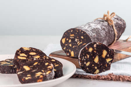 Homemade chocolate salami - dessert made from cocoa, broken biscuits, butter and eggs, with hazelnuts. White background. Copy space.