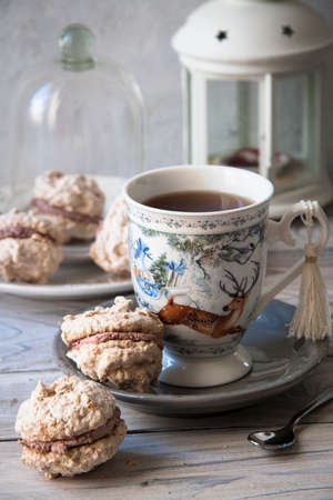 Coconut macaroons with mascarpone cream, and hot tea on winter holidays background