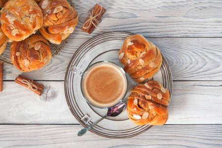 Homemade Kanelbullar - Swedish Cinnamon Buns and coffee. Top view. Wooden background.