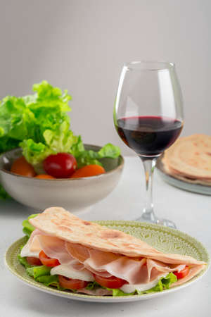 Italian flat bread Piadina Romagnola with prosciutto, mozzarella cheese, tomatoes and salad. Red wine glass.