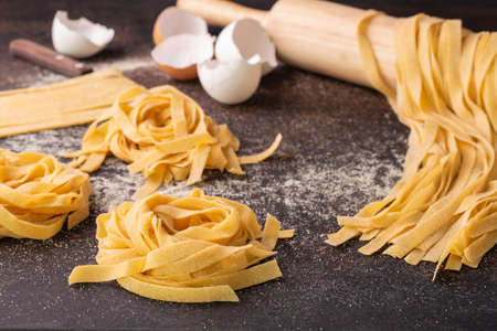 Close up of raw homemade tagliatelle, italian egg pasta on dark table
