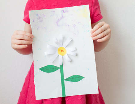 Home activities with kids: a girl holding a paper flower made from colourful paper. .