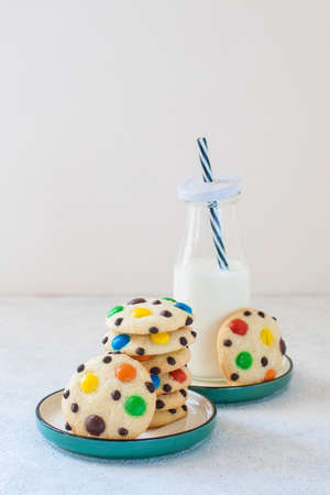 Homemade m&m's cookies with a bottle of milk.