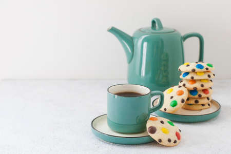 Homemade m&m's cookies with tea pot and a cup of tea.