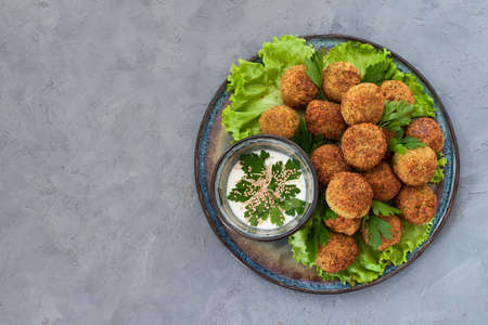 Falafel - deep-fried bals made from ground chickpeas, laid over a bed of salads, with lemons. Grey background.
