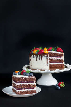 Layered chocolate cake decorated with flowers and berries on the garden table. 版權商用圖片