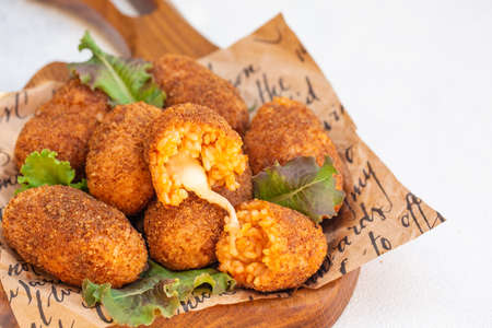 Rice balls stuffed with mozzarella cheese and deep fried. Close up. Copy space.