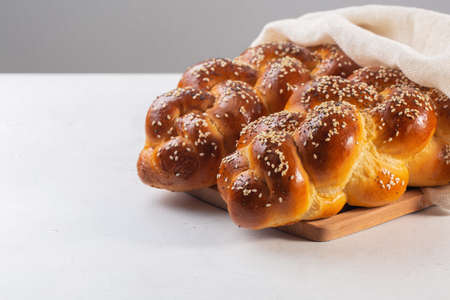 Homemade Challah with white cover - special bread in Jewish cuisine.Main ingredients are eggs, white flour, water, sugar, salt and yeast. Decorated with sesame and poppy seeds. On white table.