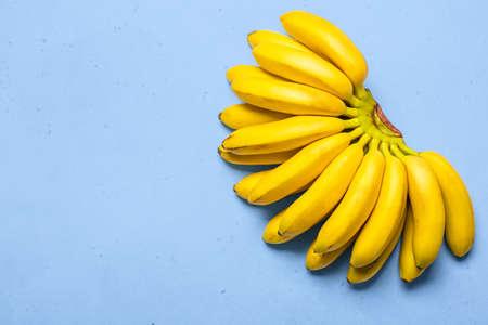 Organic rip of mini bananas on blue background.