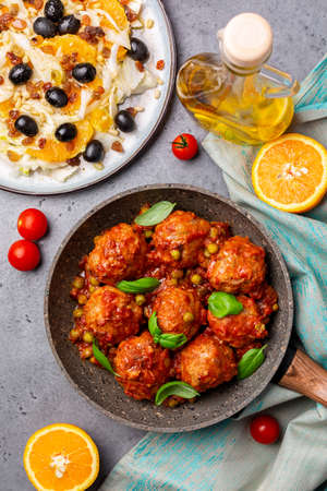 Turkey meatballs in tomato sauce with green peas and basil leaves. Flat lay, grey concrete background. Copy space.