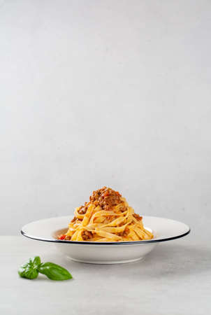 Plate with italian pasta Tagliatelle al ragu with bolognese sauce, vertical image, copy space.