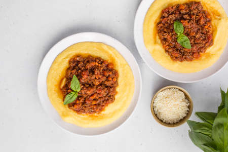 Boiled cornmeal or polenta with meat-based sauce - rag alla bolognese. White background copy space. Stock Photo