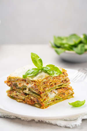 Homemade oven-baked green lasagna - Lasagne alla bolognese with spinach in the dough, ragu - meat sauce, bechamel and parmesan cheese. Fresh spinach on background. Vertical image.