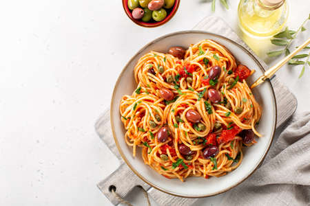 Spaghetti alla puttanesca - italian pasta dish with tomatoes, olives, capers, anchovies and parsley. Light background. Copy space.