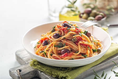 Italian lunch. Spaghetti alla puttanesca - italian pasta dish with tomatoes, olives, capers and parsley. Light background. Copy space.