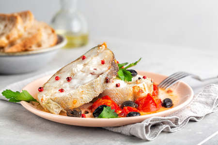 Baked cod fish steak, italian style, with tomatooes and black olives. Decorated with pink peppercorn. Close up. Archivio Fotografico