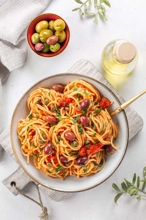 Spaghetti alla puttanesca - italian pasta dish with tomatoes, olives, capers, and garlic. Light background. Vertical image