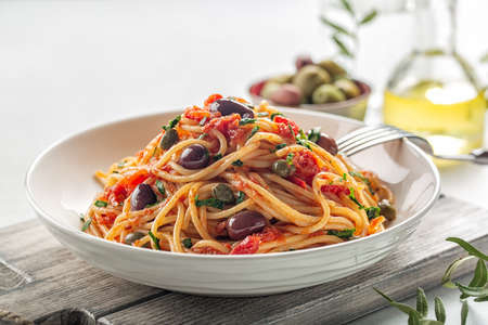 Close up of spaghetti alla puttanesca - italian pasta dish with tomatoes, olives, capers and parsley. Light background.