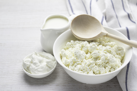 dairy products, cottage cheese, milk, yogurt, sour cream in a white dish on a white background